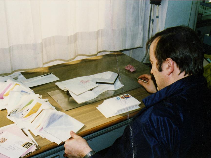 Ein MfS-Mitarbeiter sitzt an einer Heißdampfanlage. In eine Tischplatte ist eine W-förmige Öffnung eingelassen, aus der Dampf strömt. Darüber gelegt ließen sich die Briefe leicht öffnen.