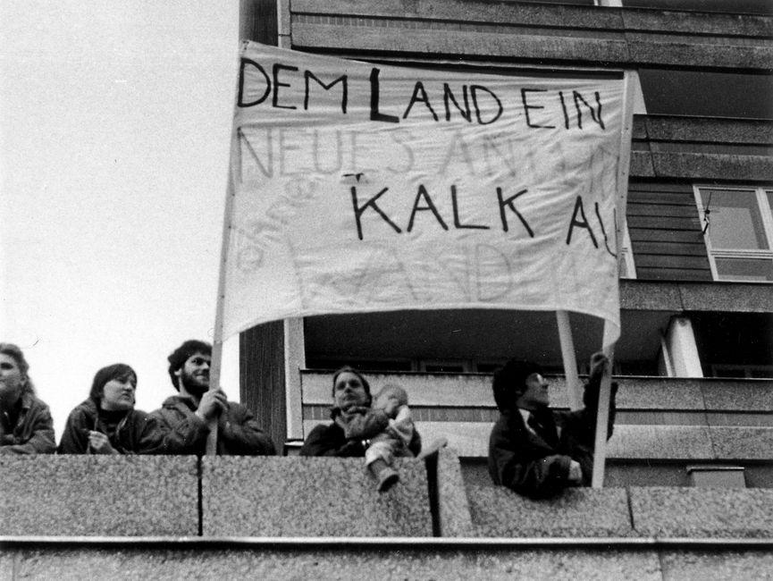 Demonstranten, die auf einem Balkon stehen. Darunter ein Kind auf dem Arm eines Erwachsenen. Zwei Demonstranten halten ein Transparent hoch. Es sind nur die Worte 'Dem Land ein neues...ohne Kalk' zu erkennen.
