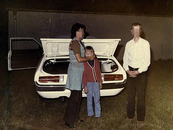 Von der Stasi vermutlich kurz nach der Festnahme der Fluchtwilligen nachgestelltes Foto um 1972. Mutter und Kind sowie vermutlich der Fluchthelfer stehen vor dem geöffneten Kofferraum eines in Westberlin gemeldeten Fahrzeugs