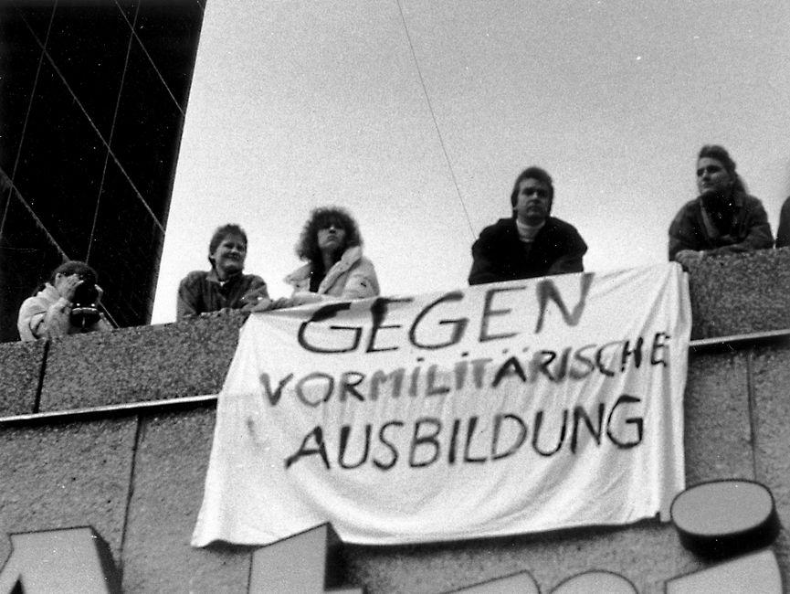 Auf dem Bild sind fünf Personen zu sehen, die auf einem Dach oder Balkon stehen. Ihre Blicke sind nach unten gerichtet. Ein Transparent mit der Aufschrift 'Gegen vormilitärische Ausbildung' ist an der Fassade angebracht. Eine Person fotografiert.