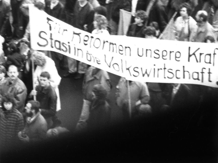 Der Betrachter des Bildes sieht auf einen Demonstrationszug. 'Für Reformen unsere Kraf Stasi in die Volkswirtschaft' ist auf einem Transparent zu lesen.