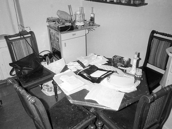 Die Stasi fotografierte bei Wohnungsdurchsuchungen Zimmer so, wie sie sie vorfand. Zu sehen ist ein Tisch mit vier Stühlen. Auf dem Tisch liegen viele Blätterstapel durcheinander.