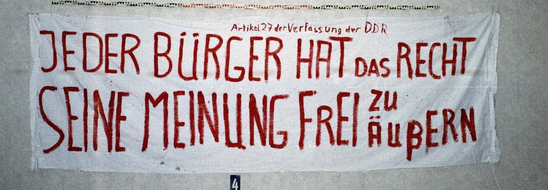 Das Bild zeigt ein abfotografiertes Transparent mit der Aufschrift: ''Artikel 27 der Verfassung der DDR / Jeder Bürger hat das Recht seine Meinung frei zu äußern'