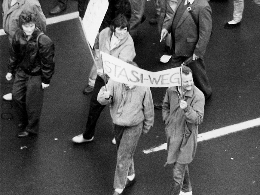 Im Zentrum des Bildes sieht man zwei Personen, die zusammen ein Transparent halten. Darauf steht 'Stasi-Weg'.