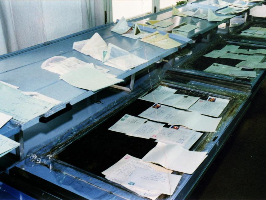 Eine Reihe Kaltdampfanlagen. Zu öffnende Briefe liegen auf einer Fläche, aus der der Dampf strömt. Bereits geöffnete Briefe liegen auf Ablagen darüber.