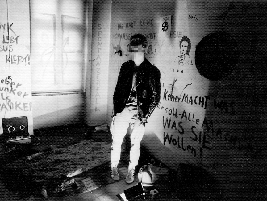 Aufnahme von einem Punk in einem besetzten Haus. Die Wände sind mit Sprüchen bemalt.