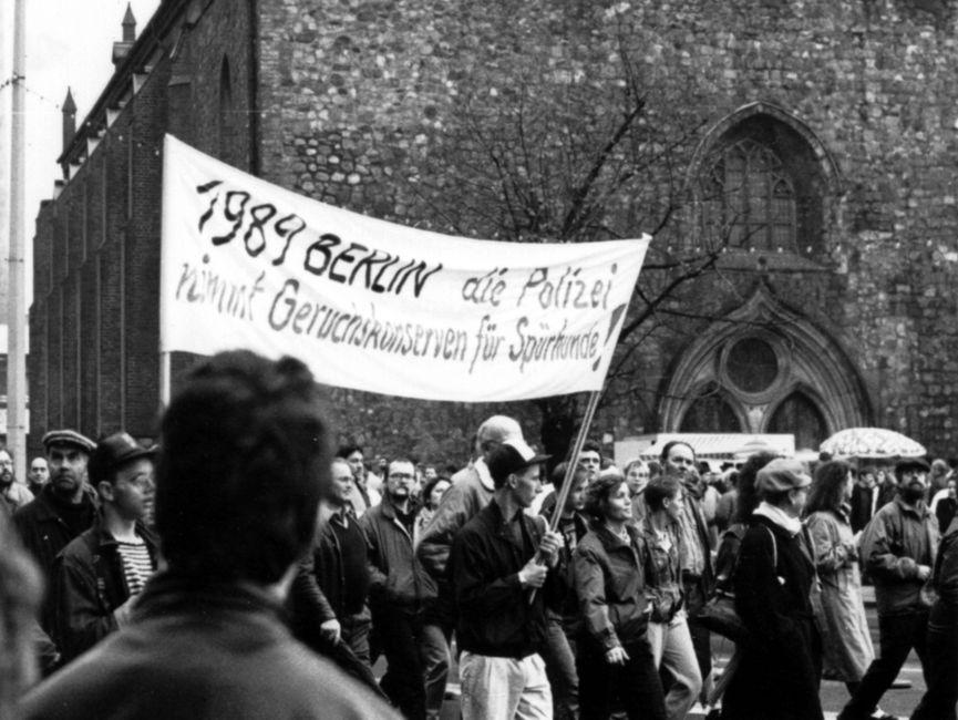 Demonstrationszug, der an einer Kirche vorbeizieht: Zwei junge Männer tragen ein Transparent mit der Aufschrift '1989 Berlin die Polizei nimmt Geruchskonserven für Spürhunde'.