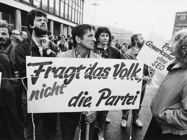 Auf dem Schwarz-Weiß-Bild sind mehrere Demonstrantinnen und Demonstranten zu sehen. Einer von Ihnen hält ein Transparent mit der Aufschrift 'Fragt das Volk, nicht die Partei'.