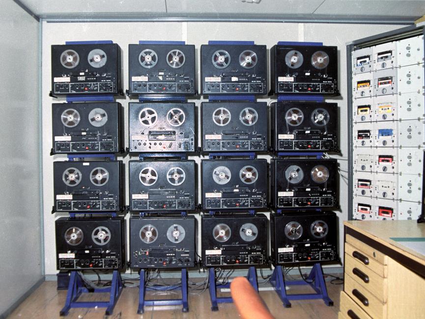 Eine Wand mit 16 Tonbandgeräten, die an eine Rufnummernselektierungsanlage gekoppelt waren.