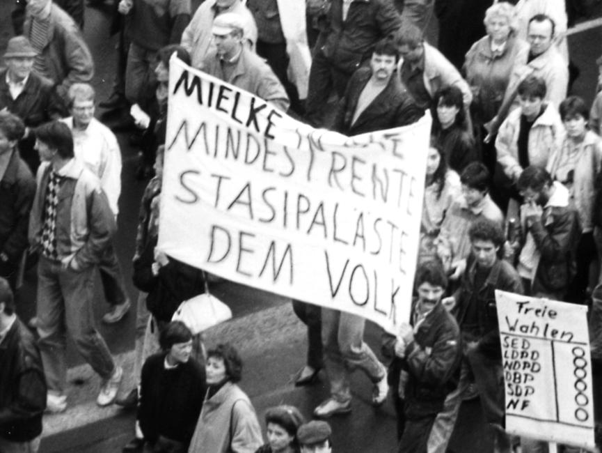 Das Bild zeigt den Blick in einen Demonstrationszug. In der Mitte des Bildes ist ein Transparent mit der Aufschrift 'Mielke [unleserlich] Mindestrente Stasipaläste dem Volk' zu sehen. Unten rechts im Bild ist ein Plakat auf dem 'Freie Wahlen SED LDPD NDPD DBD SDP NF' steht. Hinter den Parteiabkürzungen sind Kreise zum Ankreuzen.