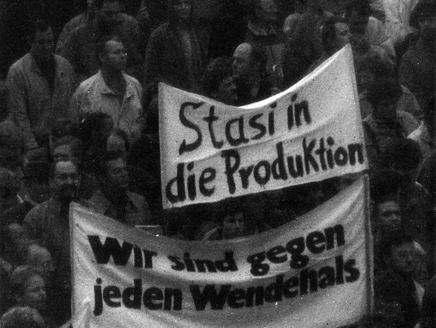 Blick auf Demonstration: Im Mittelpunkt des Bildes stehen zwei Transparente. Auf einem Transparent steht 'Stasi in die Produktion', auf dem anderen 'Wir sind gegen jeden Wendehals'.