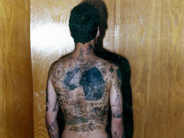 Zu sehen ist die Rückenansicht eines tätowierten Mannes.