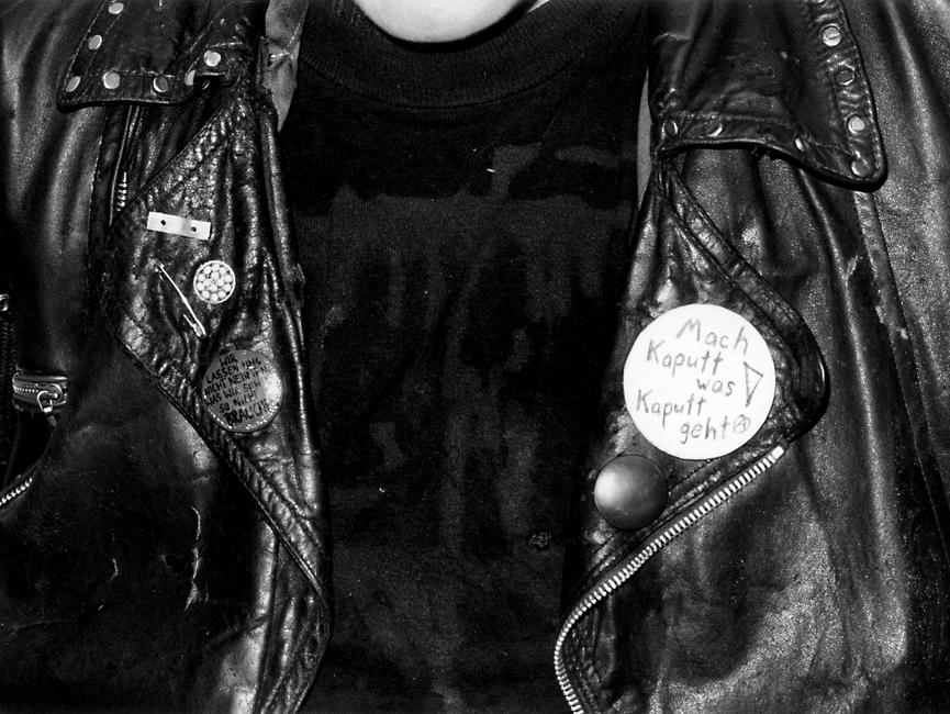 Aufnahme von einer mit Nieten besetzten Lederjacke. Auf ihr ist ein Aufnäher angebracht, auf dem steht: 'Mach kaputt was kaputt geht!'