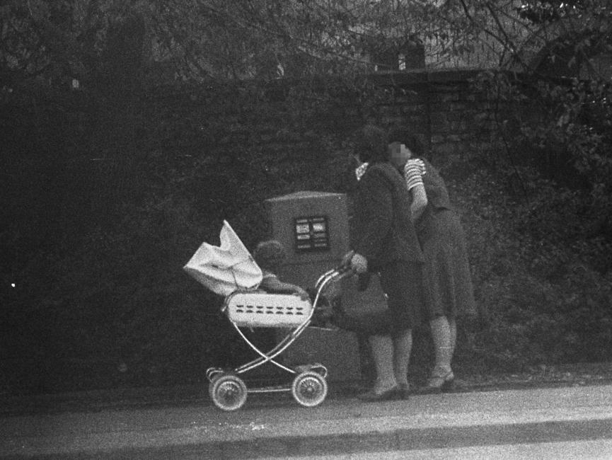 Stasi-Observation von Bürgern beim Einwurf von Post in einen öffentlichen Briefkasten. Hier stehen zwei Frauen am Briefkasten, eine davon mit Kinderwagen.