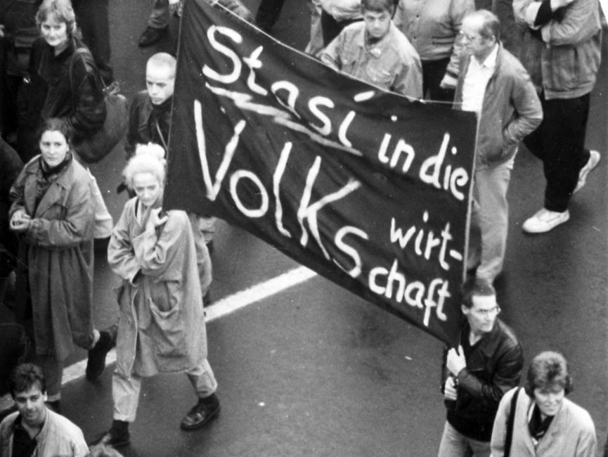 Eine junge Frau und ein junger Mann tragen inmitten einer Demonstration ein Transparent mit der Aufschrift 'Stasi in die Volkswirtschaft'.