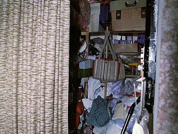 Die Stasi fotografierte die Privaträume von Bürgern. Zu sehen ist ein Schmaler Abstellraum, der bis oben mit Plastiktüten und Koffern gefüllt ist.