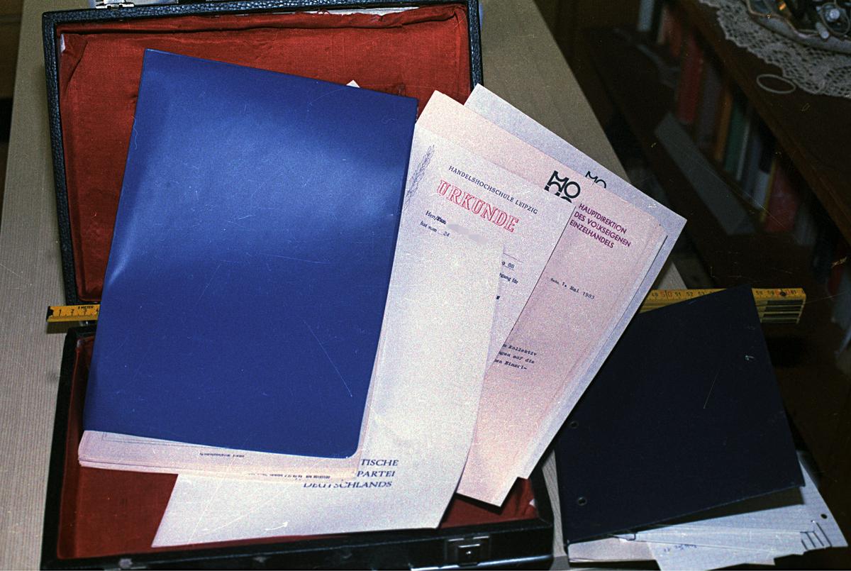 Bild eines aufgeklappten Koffers mit verschiedenen privaten Dokumenten