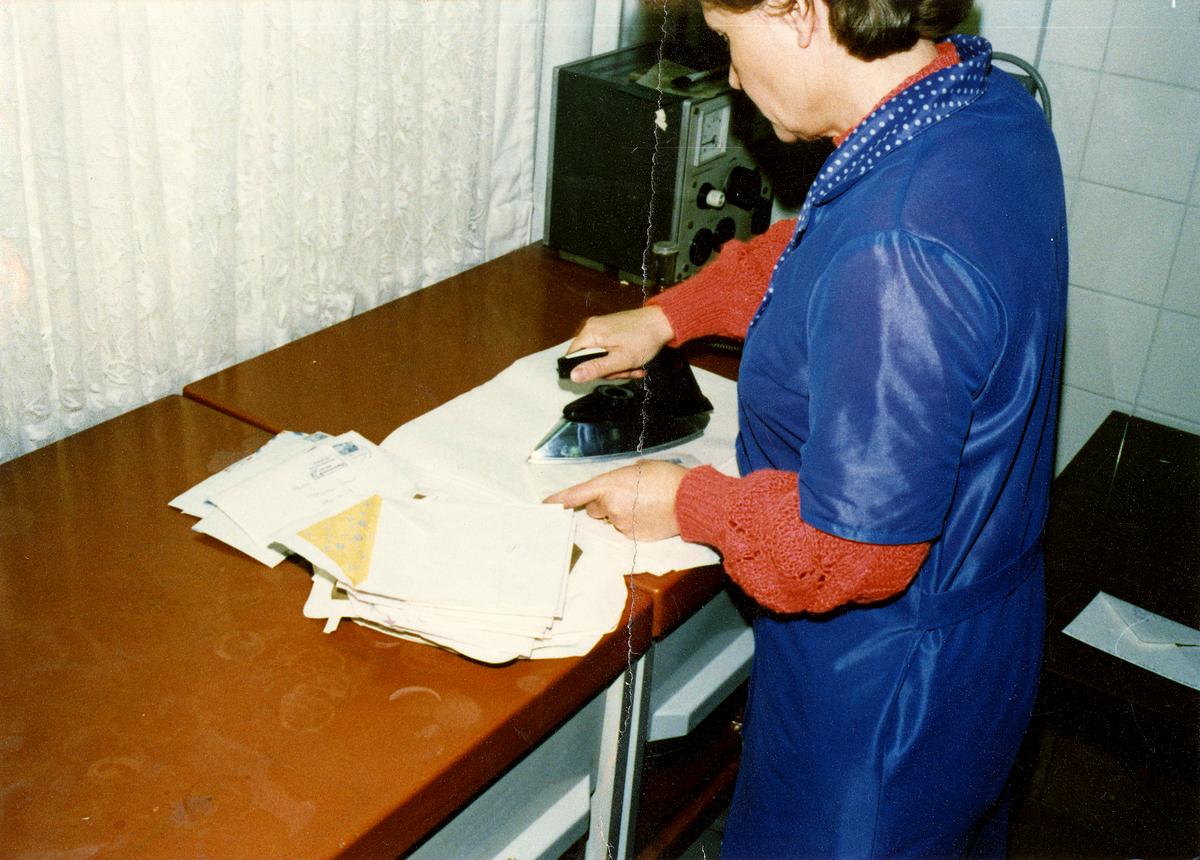 Eine MfS-Mitarbeiterin bügelt wieder verschlossene Briefe. Dadurch sollten Spuren der Öffnung beseitigt werden.
