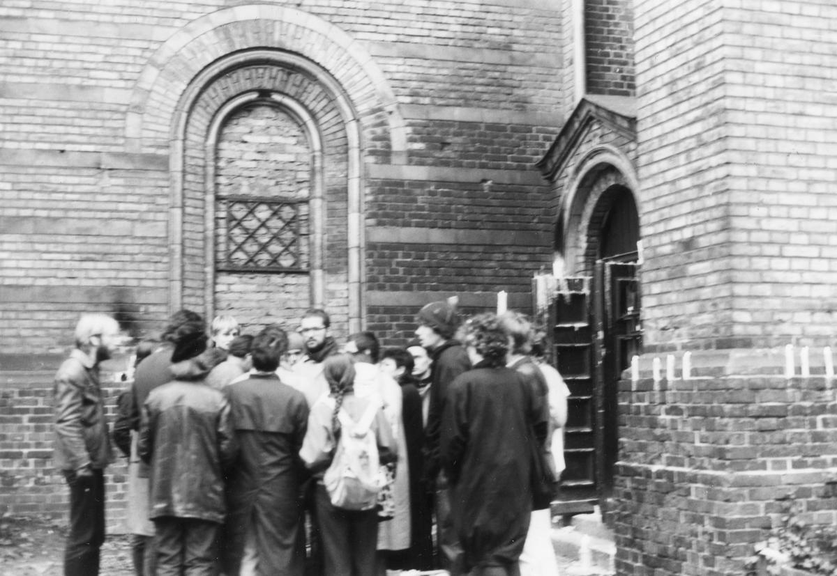 Ein Gruppe von Teilnehmern einer Mahnwache steht vor der Zionskirche. Sie protestieren gegen Festnahmen in der Umweltbibliothek Ende November 1987.