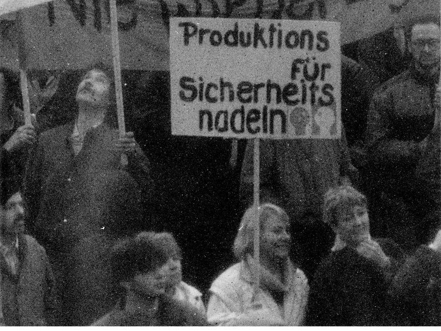 Das Bild zeigt einen Blick ganz nah in die Menschenmenge. Eine Frau hält ein Plakat mit der Aufschrift 'Produktions für Sicherheitsnadeln'.