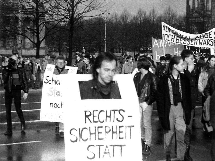 Demonstranten mit Transparenten und Plakaten. Vorne im Bild trägt ein Mann ein Transparent, worauf der Anfang des Schriftzuges 'Rechtssicherheit statt' lesbar ist.