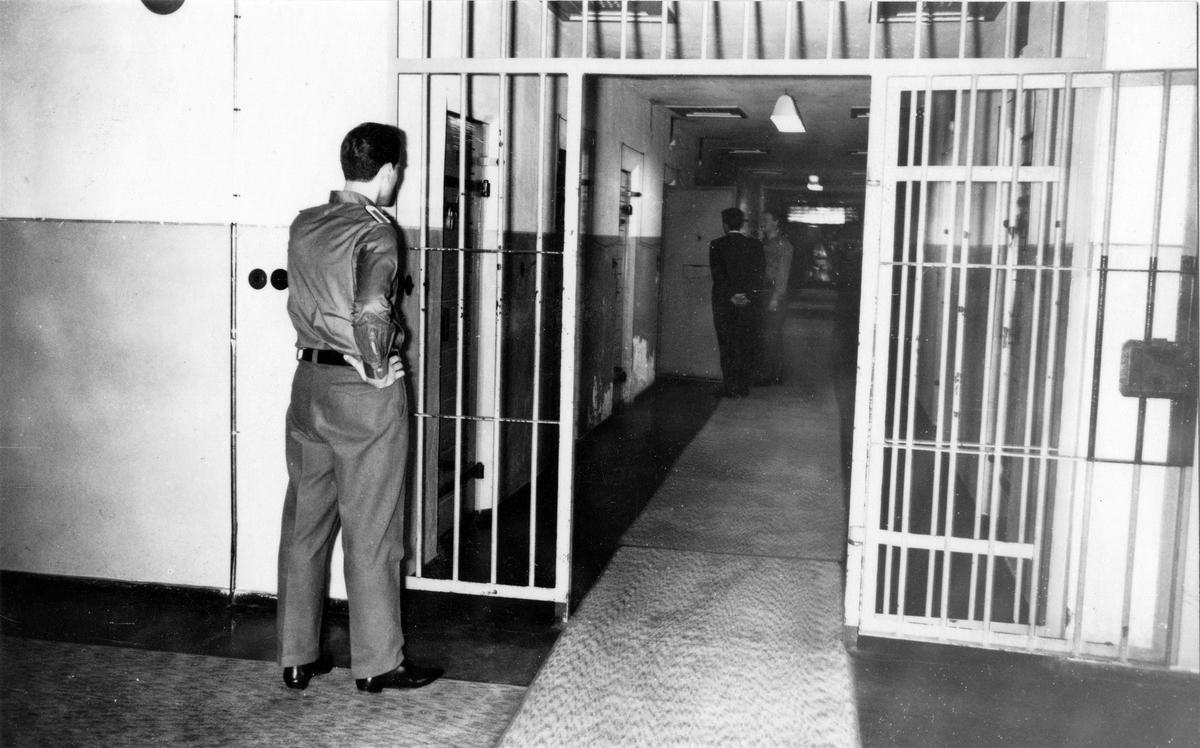 Ein Häftling wird gerade von einem Wärter in seine Zelle gelassen. Ein weiterer Wärter beobachtet das Geschehen. Fotodokumentation der Stasi über Einrichtung und Sicherungsmaßnahmen in Haftanstalten aus dem Jahr 1967.