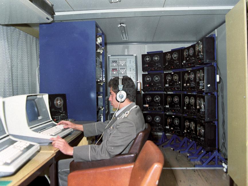 Ein MfS-Mitarbeiter an einer Rufnummernselektierungsanlage (RSA). Die abgebildete Anlage besteht aus 16 Tonbandgeräten und weiterer Technik.