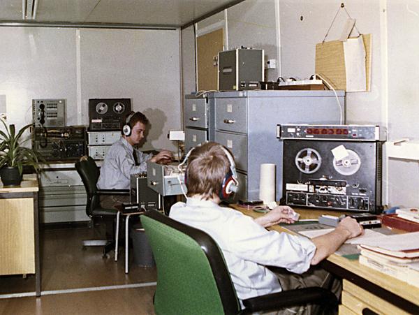 MfS-Mitarbeiter beim Abhören zuvor aufgezeichneter Telefongespräche. Zu sehen sind zwei Männer, die an Tonbandapparaten sitzen und Kopfhörer tragen.