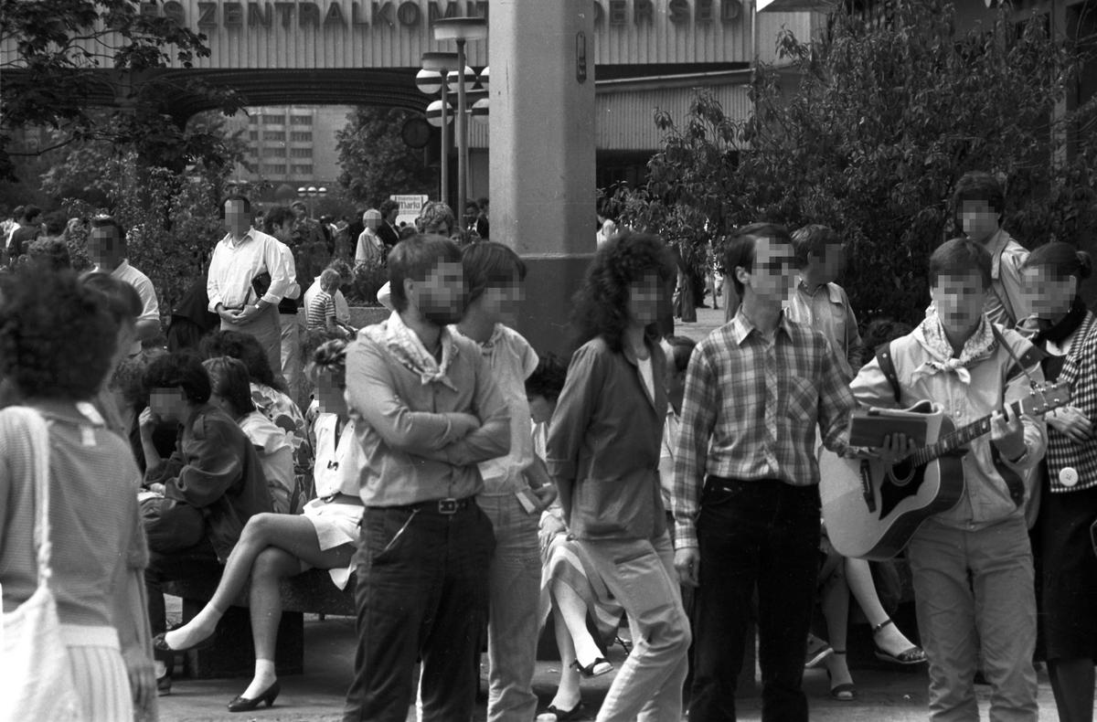 Das Bild zeigt eine größere Ansammlung von Menschen auf dem Alexanderplatz in Berlin. Einige davon sitzen auf einer Bank etwas abseits, der Rest gruppiert sich um einen Gitarre spielenden Mann.