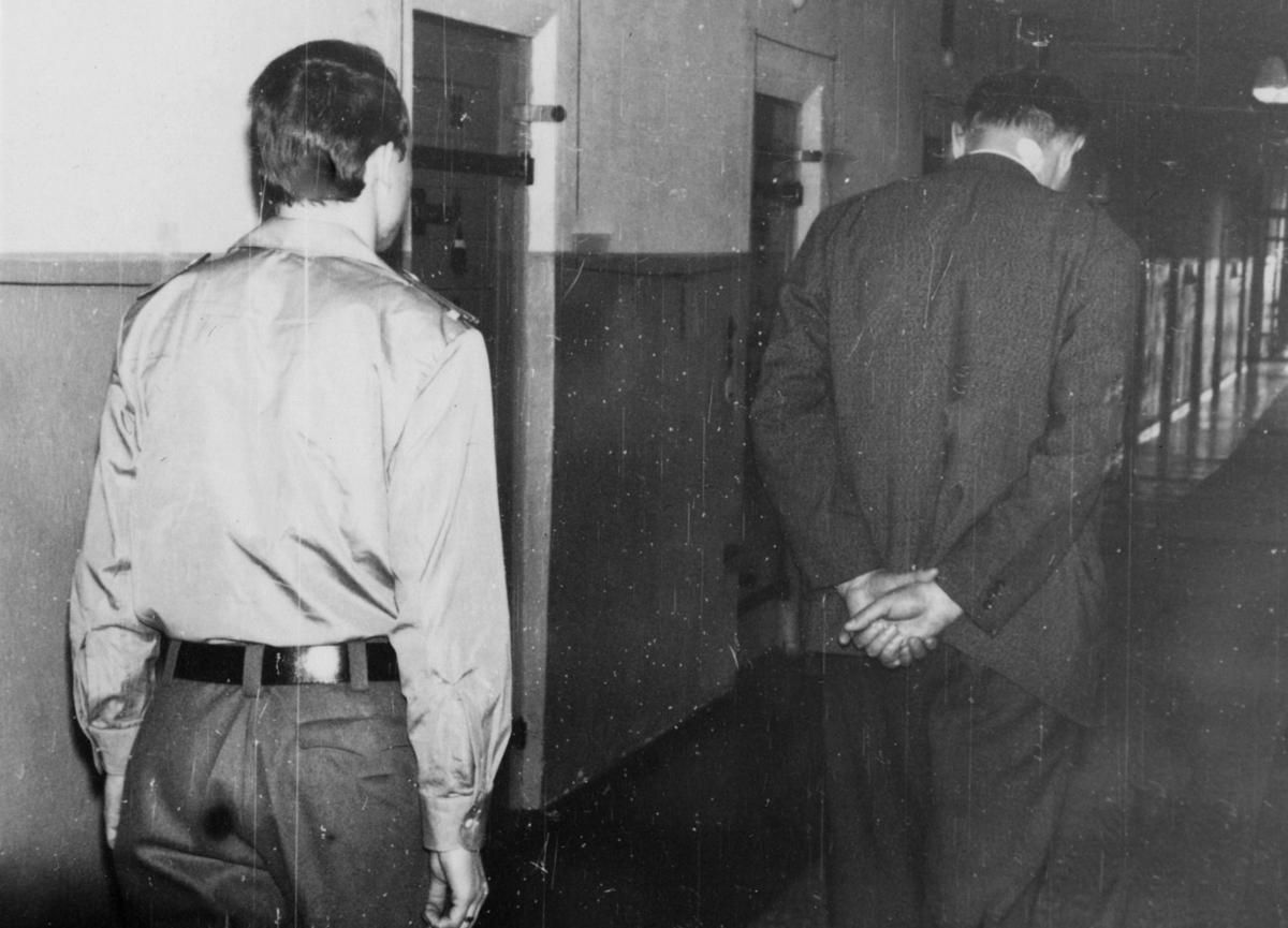 Ein Häftling geht durch den Zellengang. Ein Wärter begleitet ihn. Fotodokumentation der Stasi über Einrichtung und Sicherungsmaßnahmen in Haftanstalten aus dem Jahr 1967.