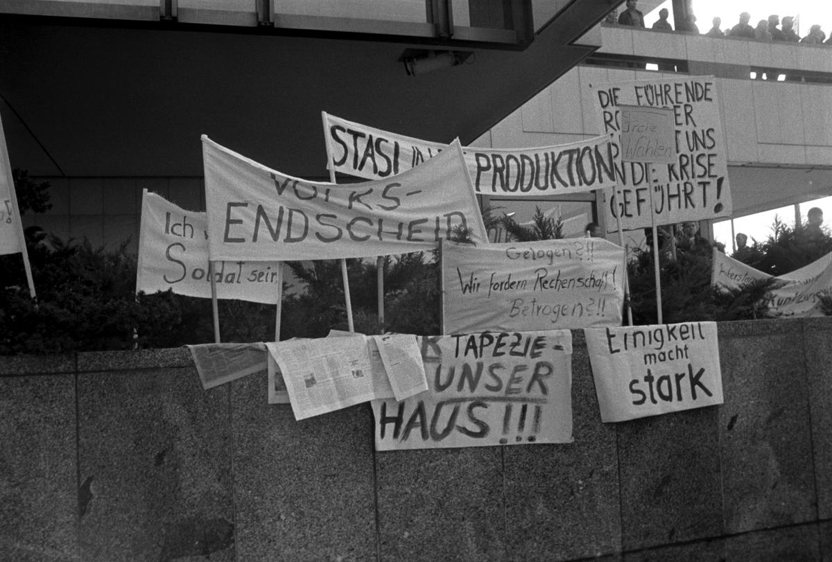 Auf einer Mauer sind mehrere Transparente aufgestellt. Die Losungen, soweit lesbar, lauten: 'Volksentscheid', 'Stasi in die Produktion', 'Ich will kein Soldat sein', 'Gelogen?!! Wir fordern Rechenschaft! Betrogen ?!!', 'Einigkeit macht stark' und 'Freie Wahlen'.