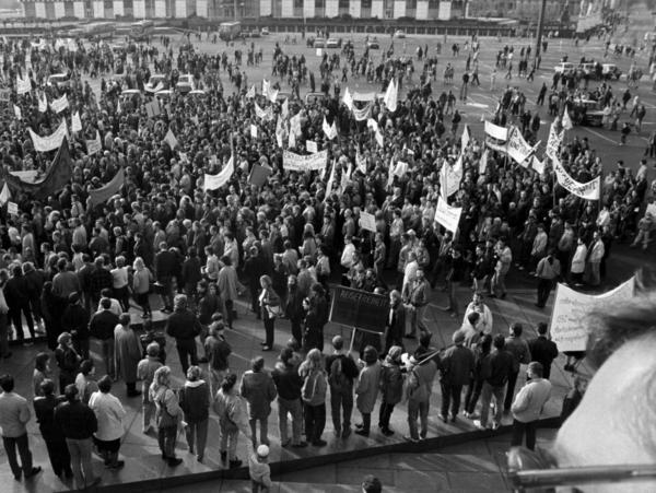 Foto von einer erhöhten Position auf den Alexanderplatz in Berlin, der mit demonstrierenden Menschen gefüllt ist. Aus der Masse ragen mehrere Transparente hervor, die aber nicht zu entziffern sind.