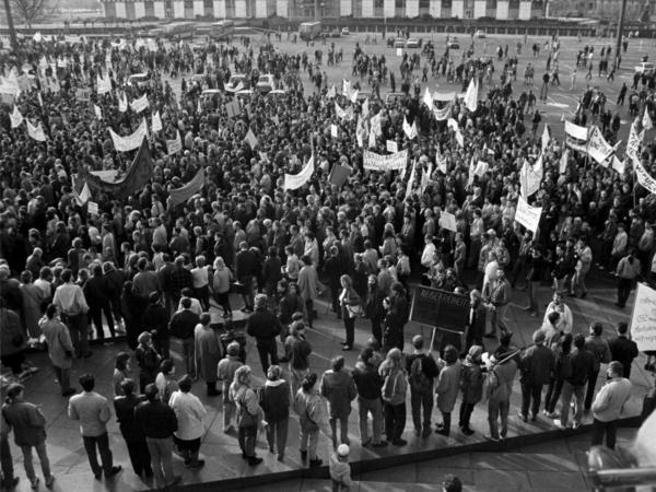 Foto von einer erhöhten Position aus auf den Alexanderplatz in Berlin, der mit demonstrierenden Menschen gefüllt ist. Aus der Masse ragen mehrere Transparente hervor, die aber nicht zu entziffern sind.