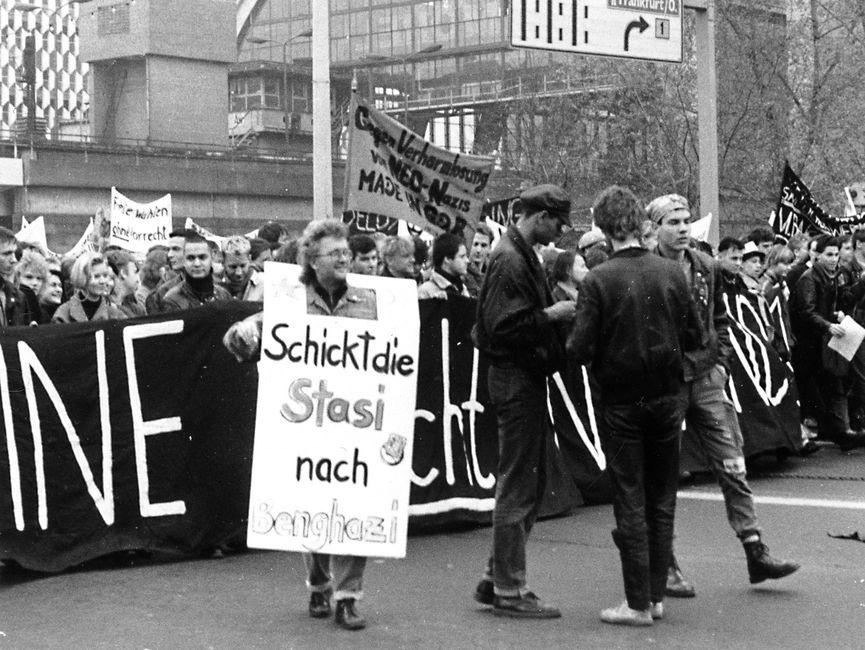 Demonstrierende vor dem S-Bahnhof Alexanderplatz. Im Hintergrund kann man das Centrum Warenhaus erkennen. Einige Demonstranten halten Transparente hoch. Auf einem steht 'Freie Wahlen ohne Vorrecht'. Es scheint der Anfang des Demonstrationszuges zu sein. Vorne wird ein Banner gehalten. Vor dem Banner steht eine Gruppe aus drei jungen Männern und ein Mann, der ein Plakat trägt mit der Aufschrift 'Schickt die Stasi nach Benghazi'.