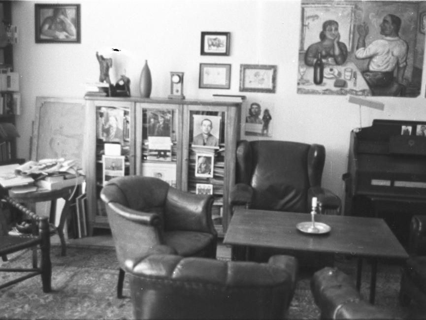 Blick in ein Zimmer, in dem ein Tisch mit Sesseln und ein gefüllter Bücherschrank stehen. An der Wand hängen mehrere Bilder, rechts ist ein verschlossener Sekretär zu sehen.