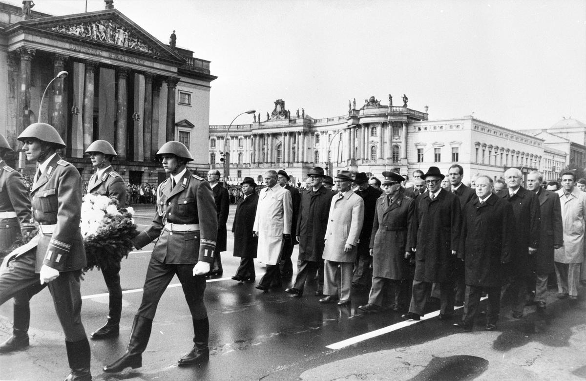 Auf dem Schwarz-Weiß-Bild sieht man den Festumzug angeführt von Soldaten und der SED-Spitze um Generalsekretär Erich Honecker auf der Höhe der Neuen Wache in Berlin-Mitte.
