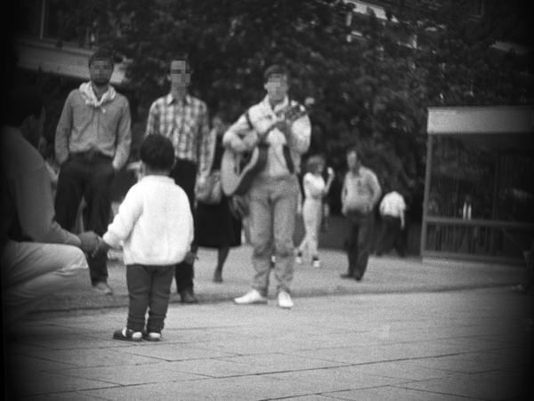 Das Bild zeigt mehrere Menschen auf dem Alexanderplatz in Berlin. Rund um die Aufnahme ist ein kreisrunder, Schatten zu sehen. Vermutlich wurde das Foto aus einer präparierten Tasche oder einem anderen Gegenstand durch ein Loch heraus aufgenommen. Die Perspektive liegt nahezu auf Bodenhöhe. Im Zentrum stehen drei Männer. Einer von ihnen spielt Gitarre. Vor ihnen steht ein Kind. Rund um sie herum sind weitere Personen zu sehen.