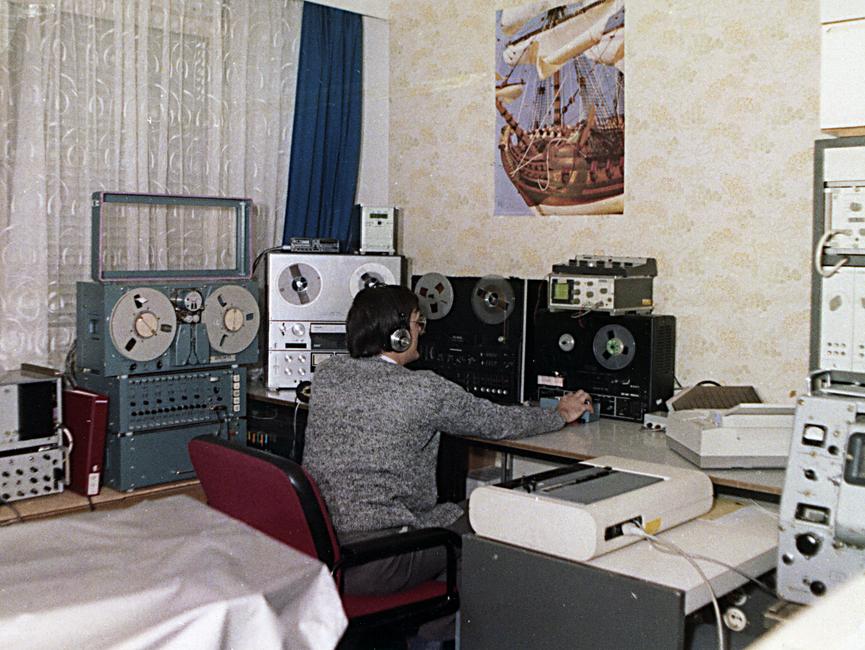 Ein Mitarbeiter der Hauptabteilung III des MfS an einem Arbeitsplatz mit Abhör- und Fernmeldetechnik.